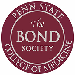 "A circular red symbol, with ""Penn State College of Medicine"" in a ring around the edge, with ""The Bond Society"" in the middle."