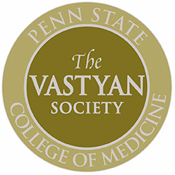 "A circular yellow symbol, with ""Penn State College of Medicine"" in a ring around the edge, with ""The Vastyan Society"" in the middle."