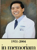 "A studio portrait of Dr. Mark J. Young, in a lab coat and tie, with the words 1951-2004 and ""In Memoriam"" underneath him."