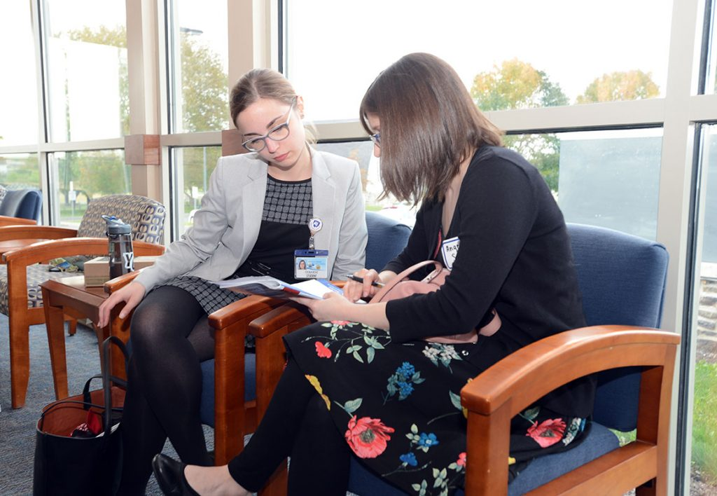 Graduate students Cecilia Bove and Angela Snyder, both PhD candidates in Neuroscience, review the events of Penn State College of Medicine Career Day 2017. The two women are pictured sitting in front of a window, looking together at a book.