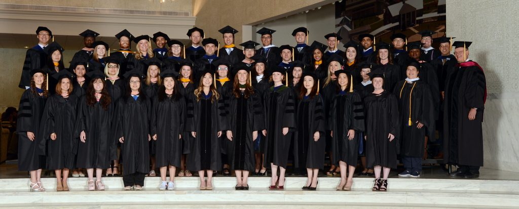 A large group of people in graduation gowns are seen in the foyer of a large stone building. They are graduate students at the Penn State College of Medicine, in May 2017.