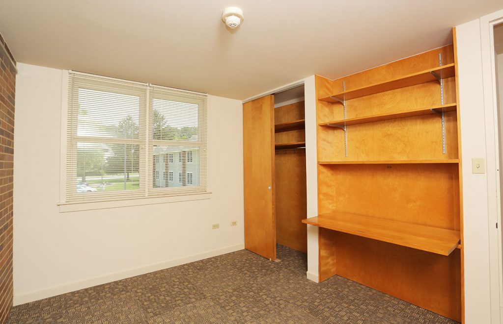 A photo of a bedroom in University Manor East at Penn State College of Medicine shows a window, a closet, a desk and a bookshelf.