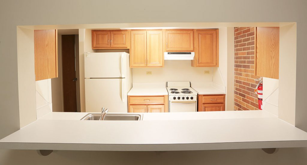 A picture of a galley kitchen at University Manor East at Penn State College of Medicine shows a refrigerator, cabinets, stove and countertop.