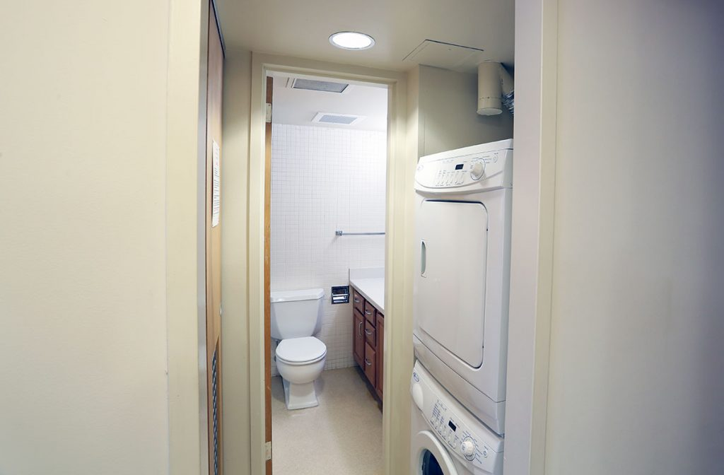 A photo of the bathroom and laundry area at University Manor East at Penn State College of Medicine shows a stacked washer and dryer and a bathroom with sink and toilet visible beyond the laundry area.