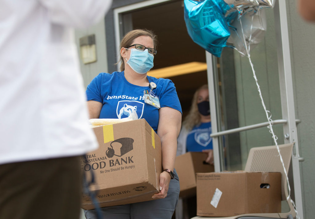 Ashley Visco is pictured carrying a large cardboard box during a eptember 2020 food distribution.