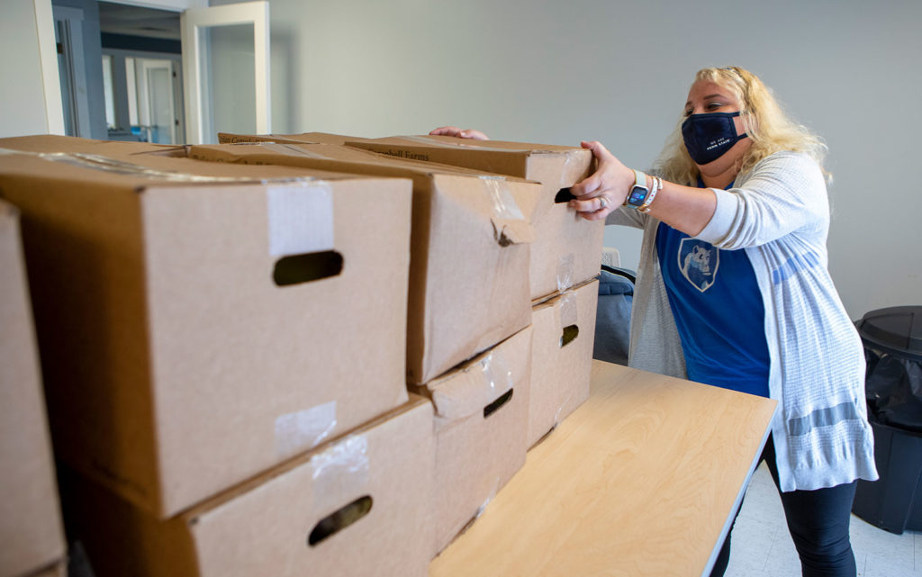 Deanna Dubots is pictured lifting a box down from a stack of boxes during a September 2020 food distribution.