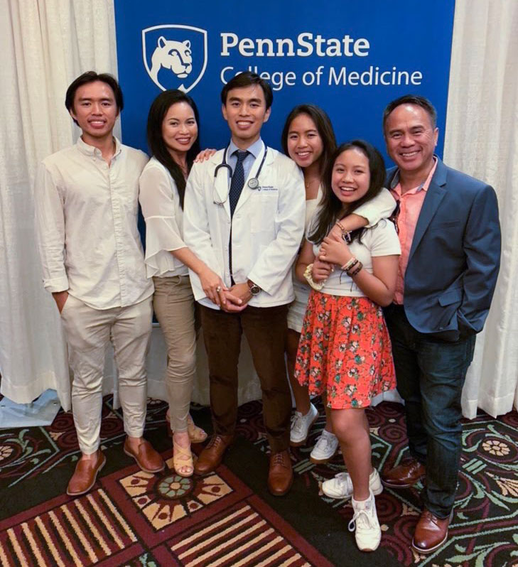 Chandat Phan, second-year medical student in 2019-2020, is seen standing with his family in front of a Penn State College of Medicine sign.