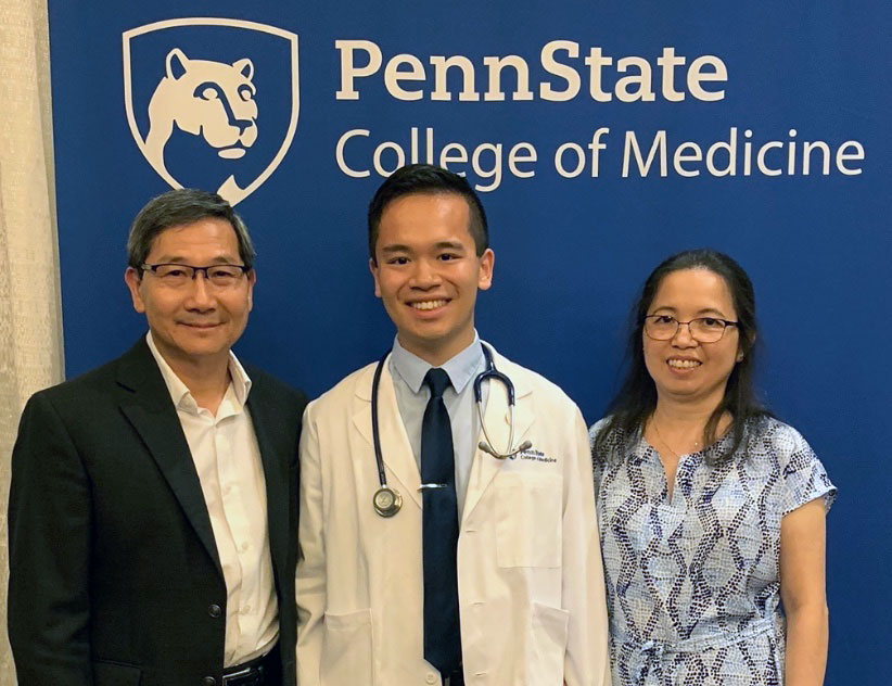 Don Hoang, a second-year medical student in 2019-2020, is seen with his family in front of a Penn State College of Medicine sign.