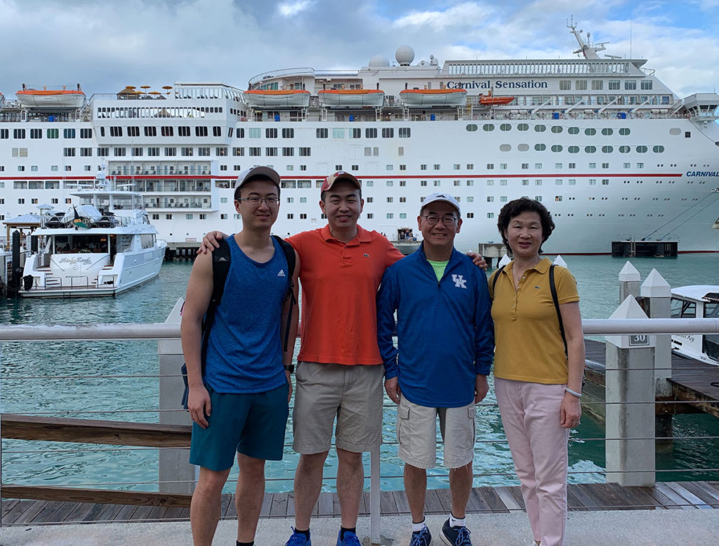 Jay Yang, a second-year medical student in 2019-2020, is pictured standing with his family in front of a large cruise ship, on a dock.