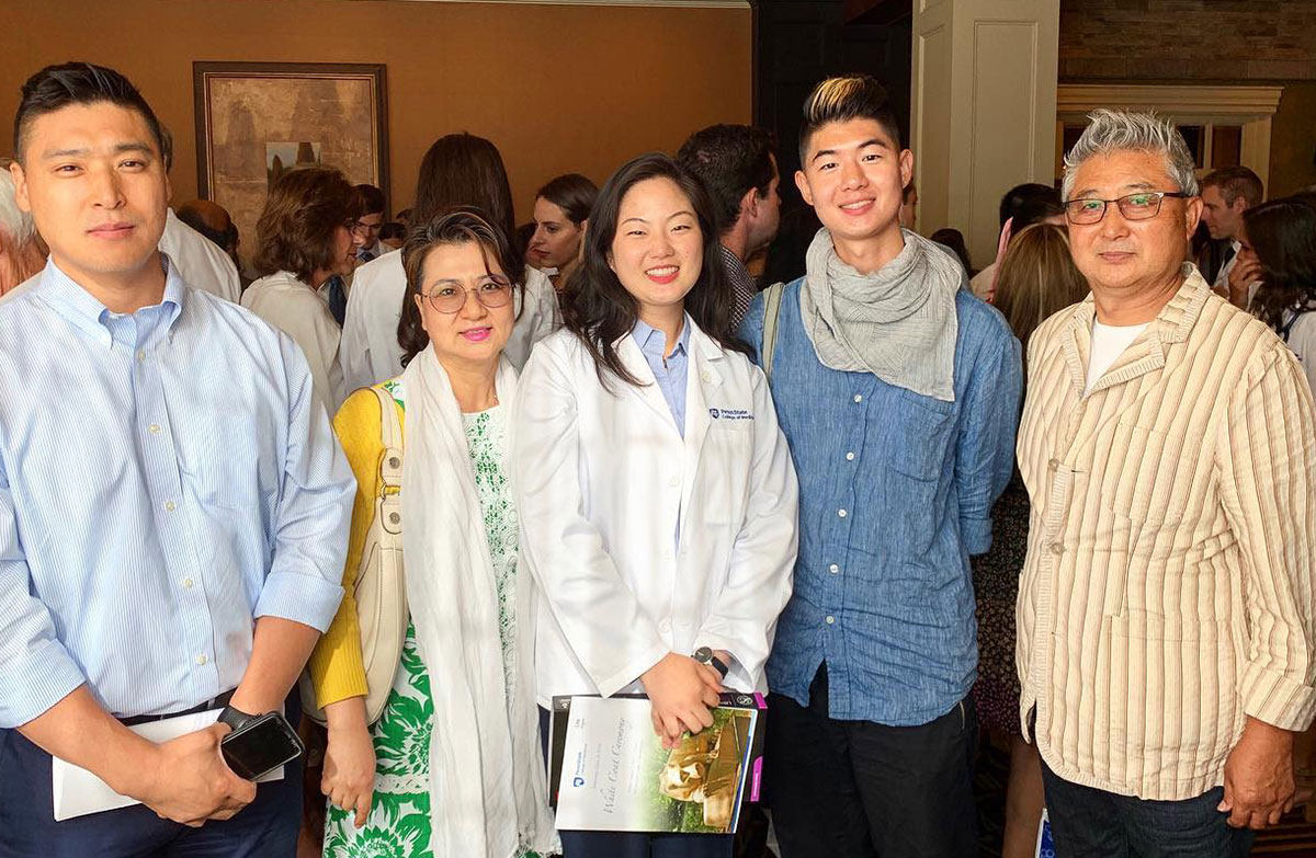 Jungeun Jasmine Lee, a second-year medical student in 2019-2020, is seen standing her family in a crowded room.