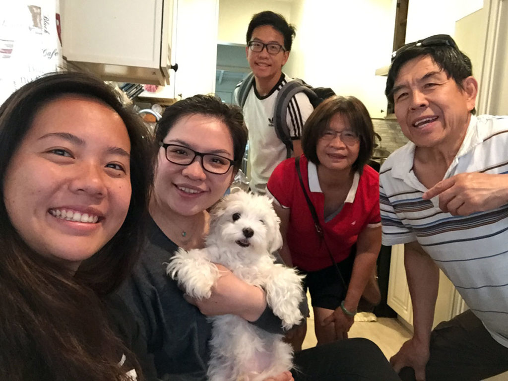 Melody Wang, a second-year medical student in 2019-2020, is pictured standing in a room with her family. One family member is holding a small dog.