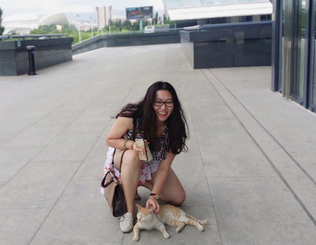 Sage Gee, a second-year medical student in 2019-2020, is seen kneeling and petting a cat.